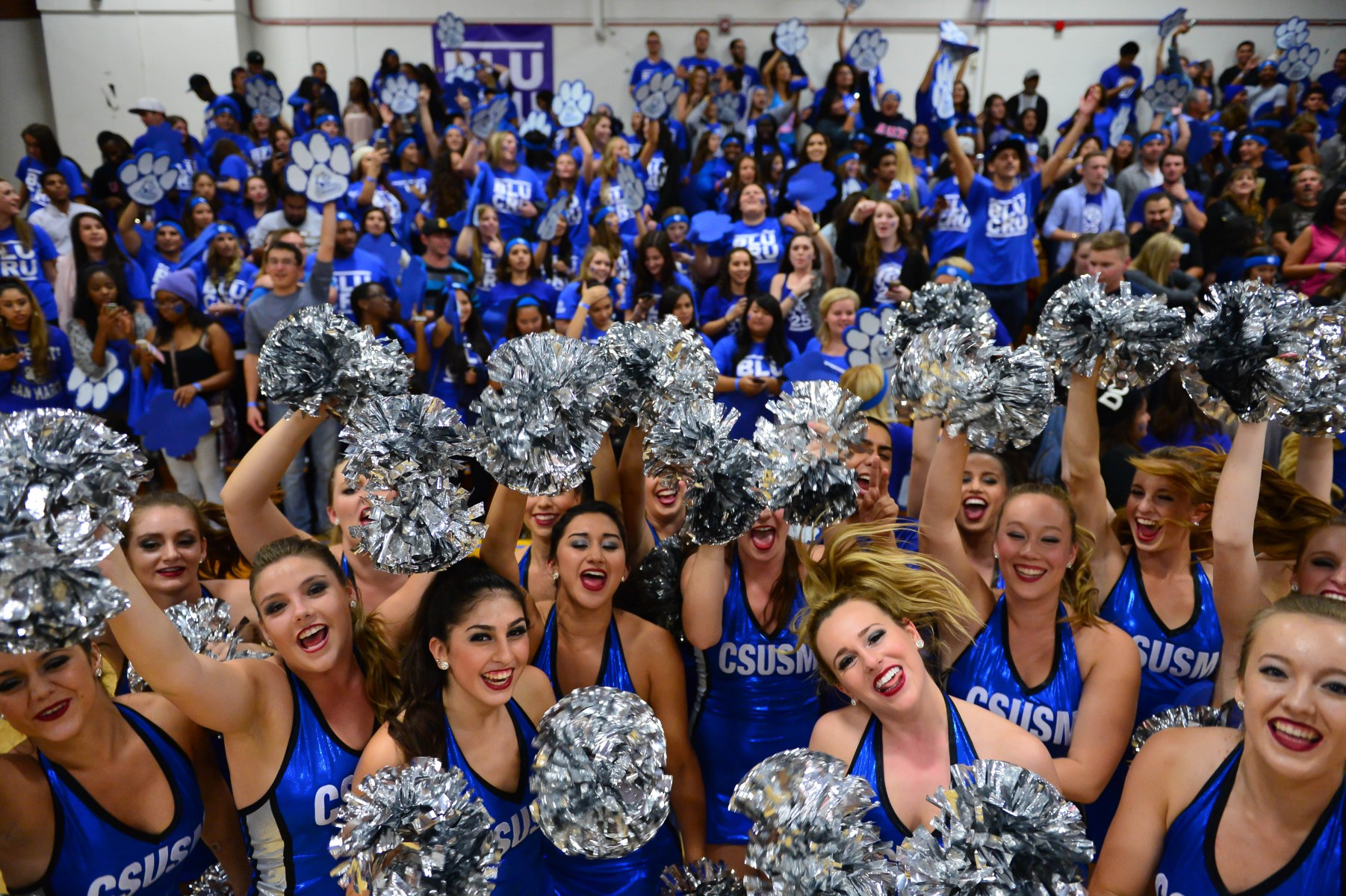 Dance Team and fans cheer on the Cougars at a Homecoming basketball game.