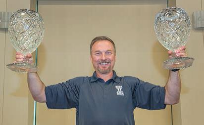 TT&R General Manager Tim Aydt proudly hoists two back-to-back President's Award trophies at a luncheon celebration at Owens Community College in Findlay, Ohio. The new trophy will take a road trip to other TT&R locations.