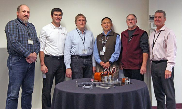 The Power Solutions engineering team stands with a model of their newly-patented cooling design