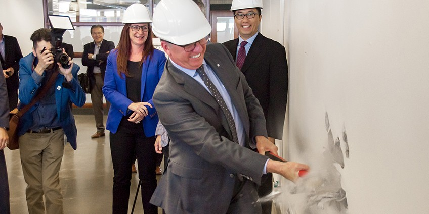 In a ceremonial sledgehammering, UAlberta president David Turpin takes a swing at a wall that is coming down to make way for the TEC Edmonton Merck Accelerator.