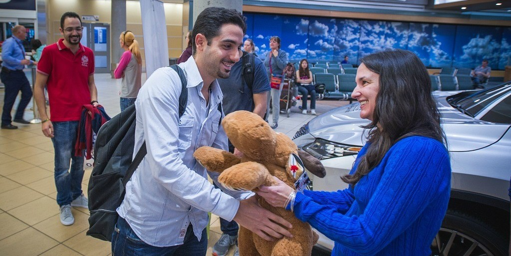 Warm fuzzy welcome: Aref Sayegh is greeted with a stuffed moose from volunteer Michelle Garcia Vega, a linguistics PhD student. (Photo: University of Alberta International)