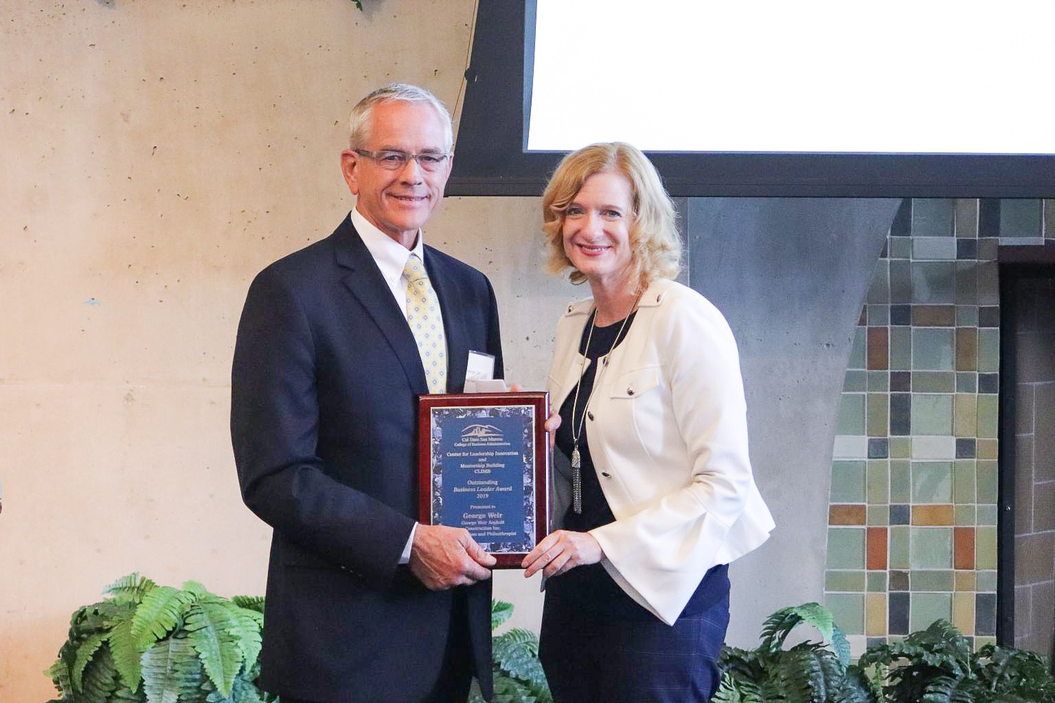 Escondido businessman George Weir receives the 2019 Outstanding Business Leader of the Year award from CSUSM President Ellen Neufeldt.