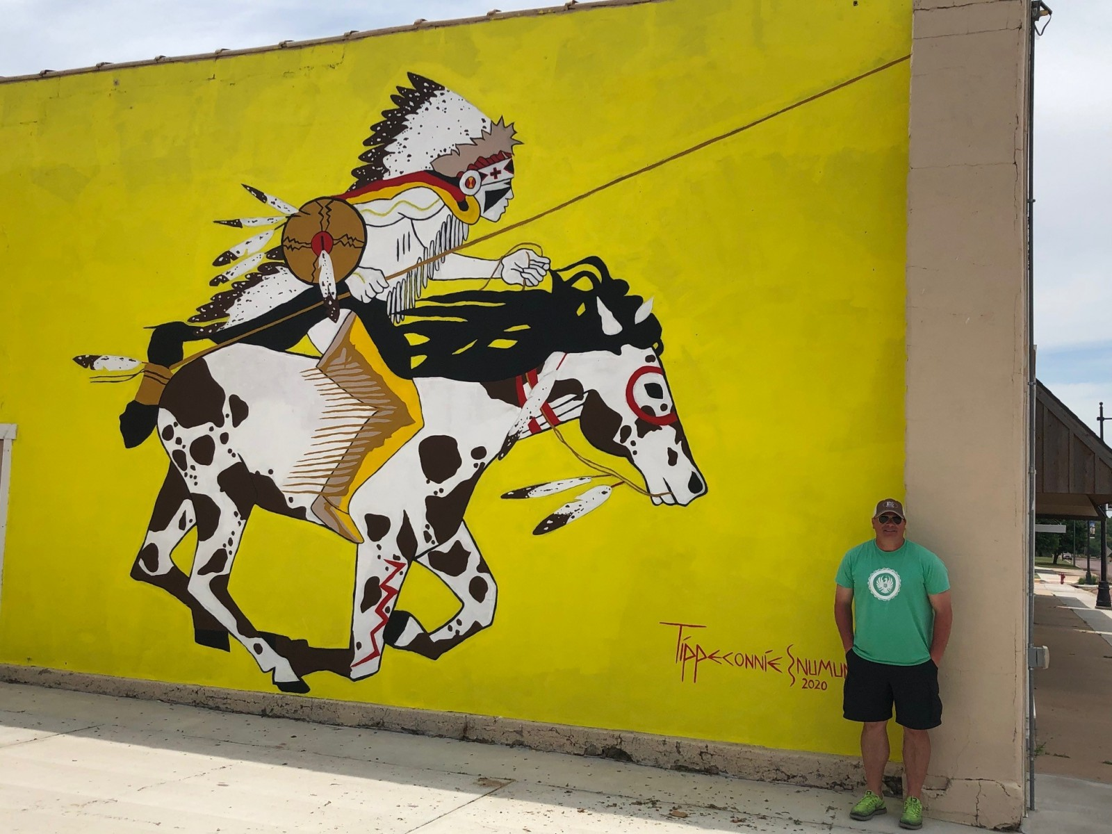 "American Indian Studies professor Eric Tippeconnic stands in front of ""Yamparika Comanche,"" the wall-size mural he painted in Medicine Lodge, Kan., over the summer."