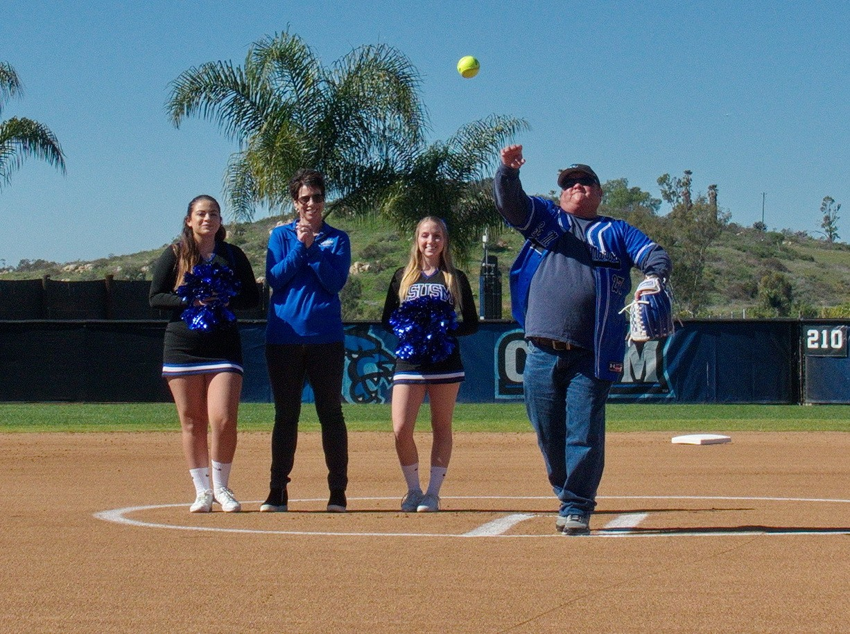 Fox Russell throws out the first pitch at a CSUSM softball game.