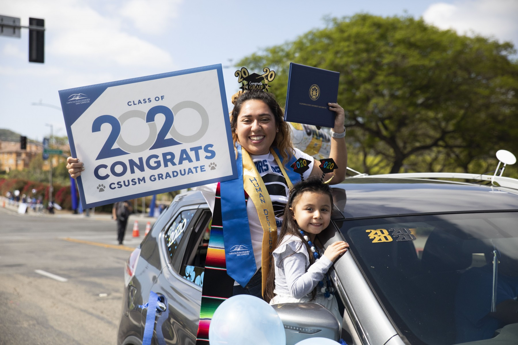 A member of the Class of 2020 holds a sign and her diploma cover during Graduates on Parade.