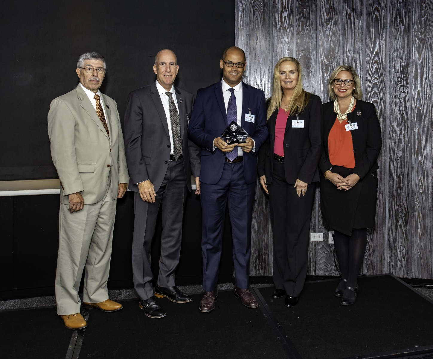 Lamine Secka (center) received an award as national sector chief of the year from InfraGard, the FBI's public-private partnership, last fall.