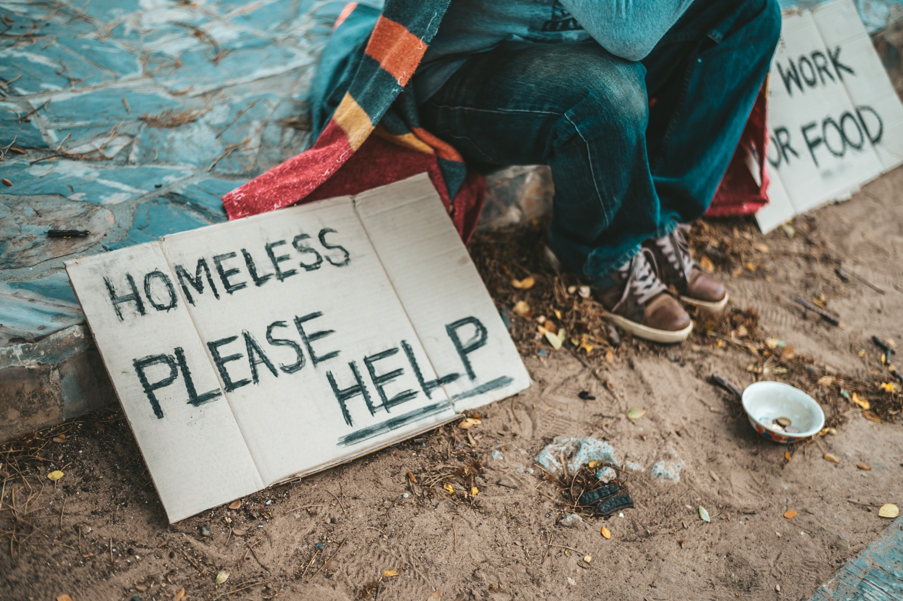 """A person sits on a curb with a cardboard """"Homeless, Please Help"""" sign"""