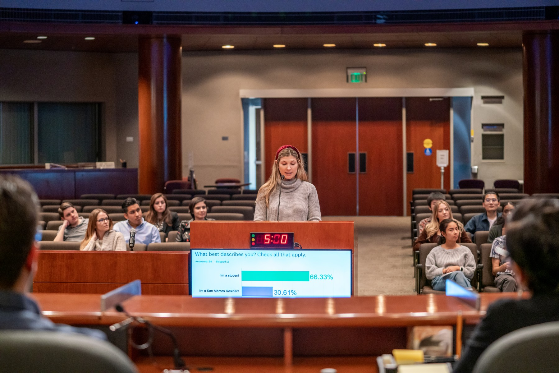 Art, Media and Design student Mackenzie Underwood addresses San Marcos city officials at City Hall during a presentation last month as part of the Democracy in Action program. Photo by Chandler Oriente