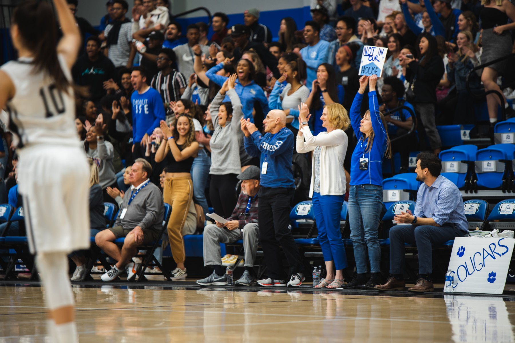 CSUSM President Ellen Neufeldt cheers on the women's basketball team with longtime university supporters Carleen Kreider and Dick Lansing on Tuesday night. The Cougars beat Sonoma State to advance to the CCAA Tournament semifinals.
