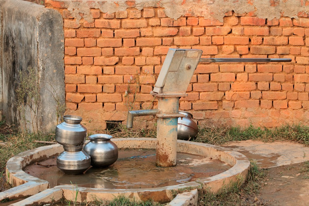 stock-photo-old-hand-operated-water-pump-and-water-containers-in-rural-india-625821380.jpg