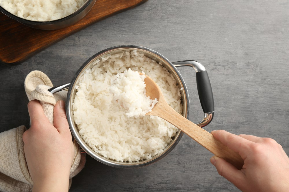 stock-photo-woman-mixing-cooked-rice-with-spoon-in-saucepan-601739936.jpg