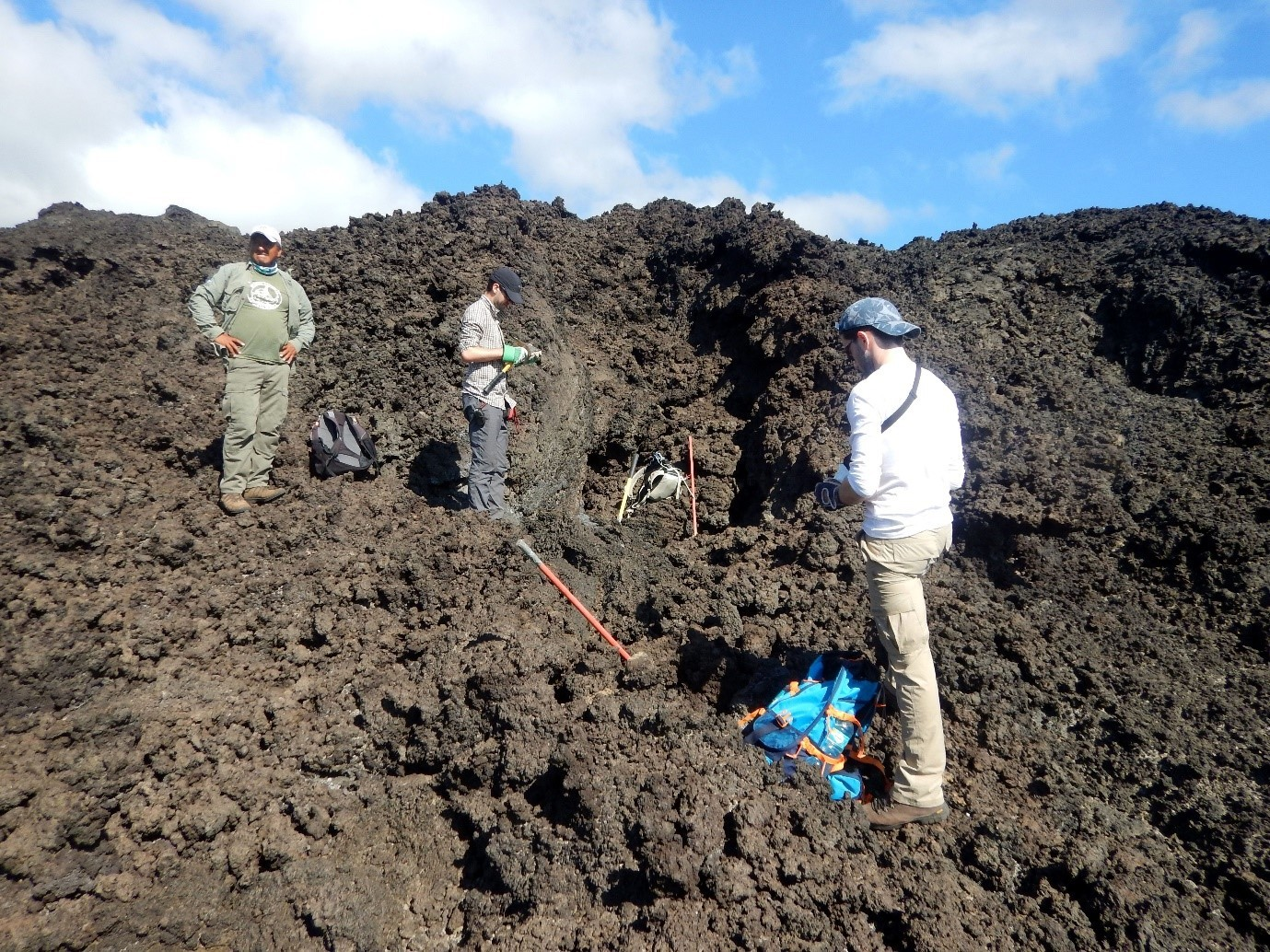 The team collects samples from solidified lava flows on Wolf volcano with assistance from a Galápagos National Park ranger, credit Dr Benjamin Bernar
