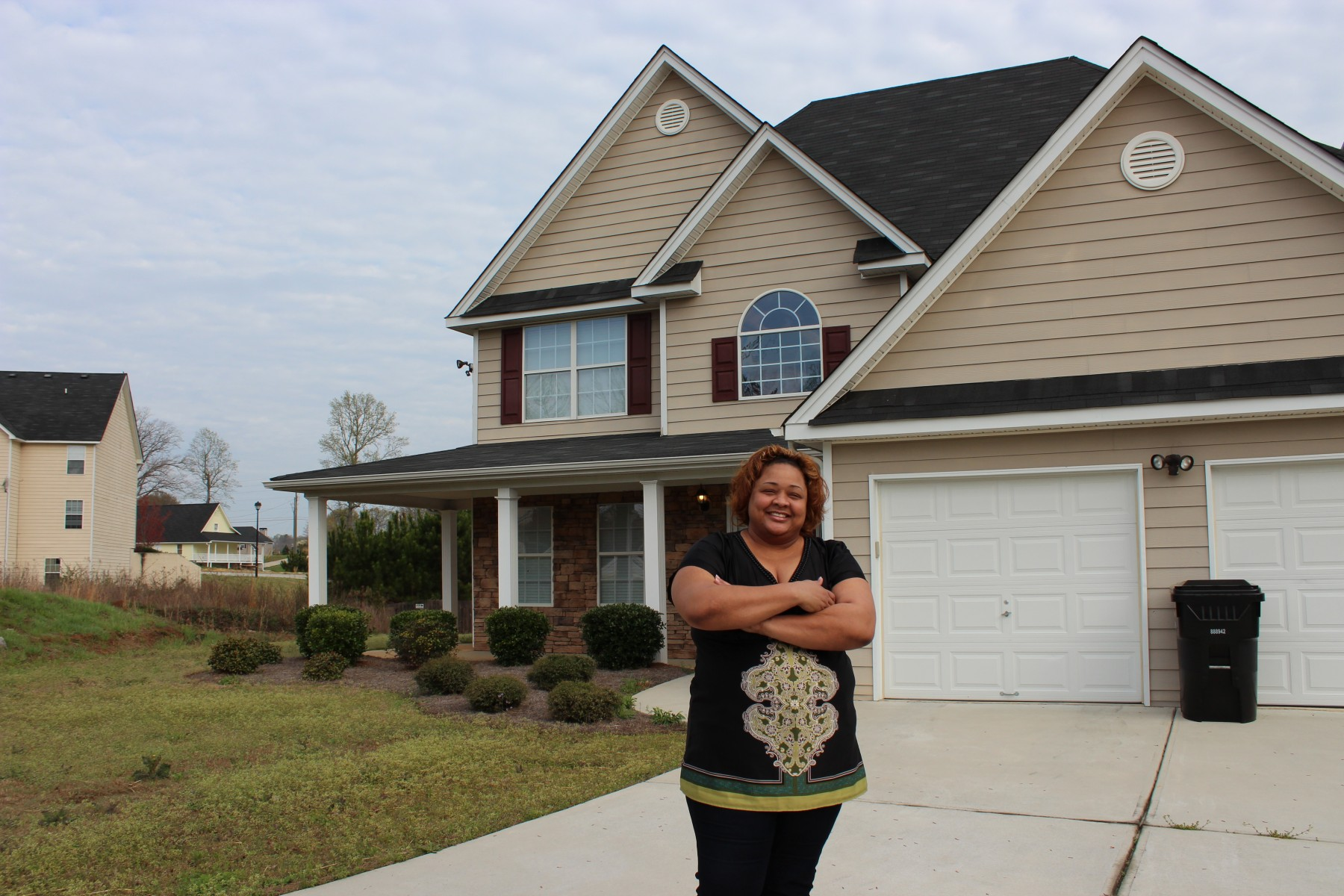 Tracey in front of her home