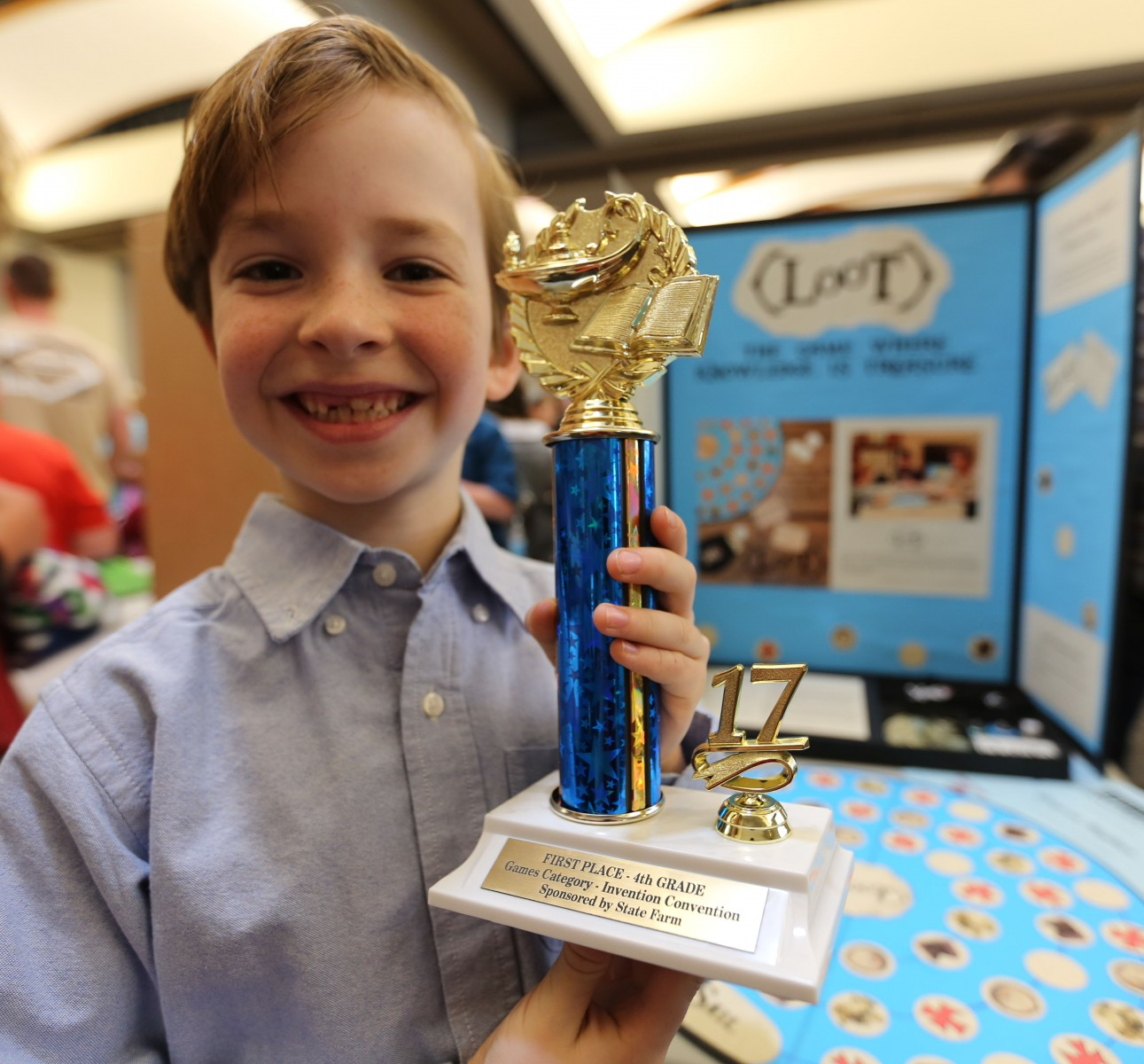 A winner shows off his Invention Convention trophy