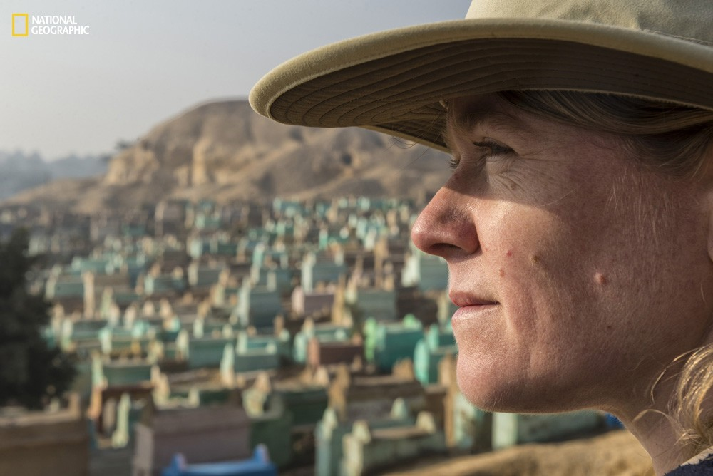 National Geographic Fellow Sarah Parcak stands in front of the cemetery that surrounds the Middle Kingdom site of El Lisht in Egypt. Looting pits dot the hills in the background.