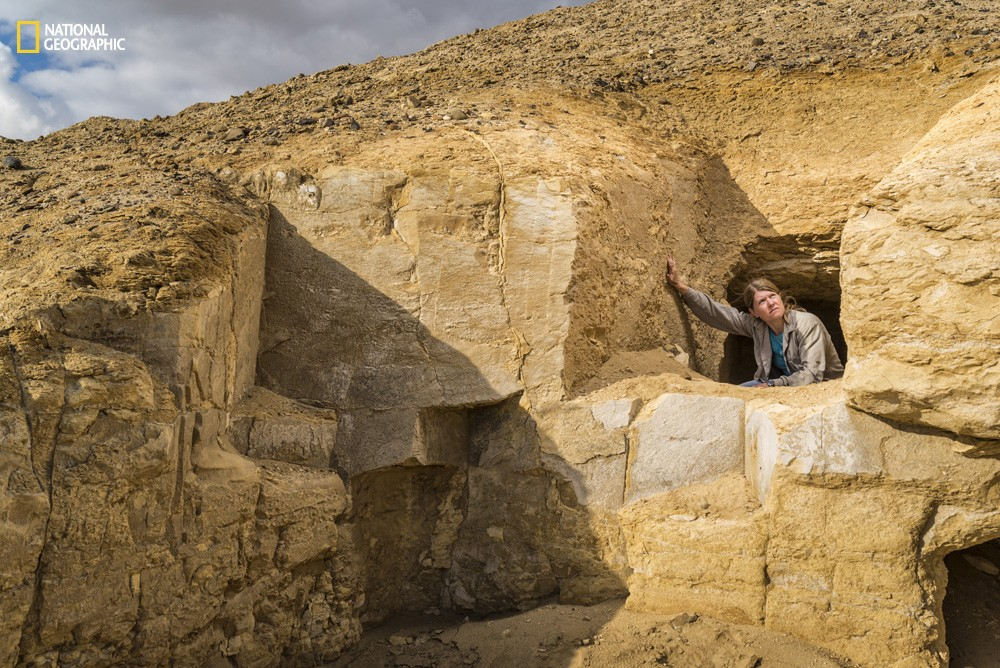 National Geographic Fellow Sarah Parcak kneels inside a looted tomb near the Middle Kingdom site of El Lisht in Egypt.