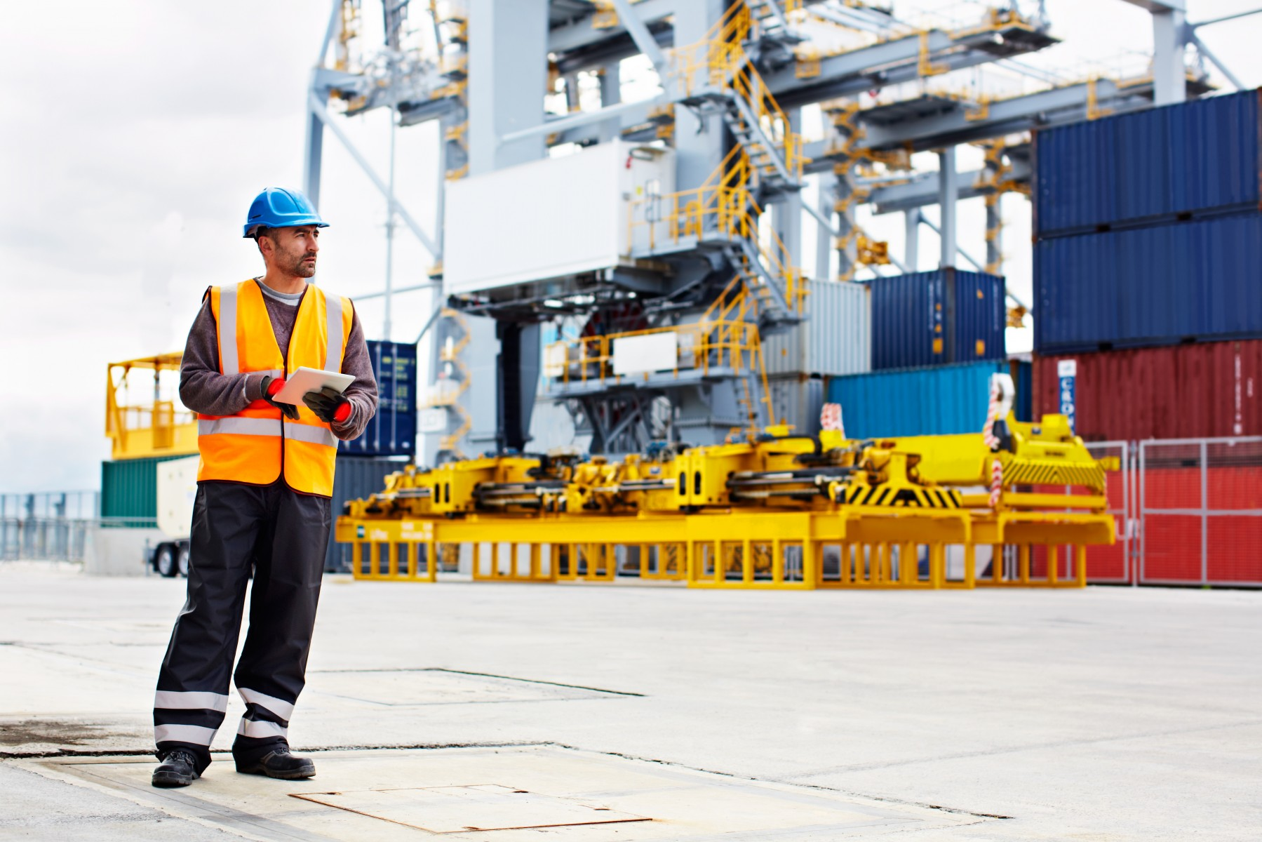 Male maritime worker wearing safety gear and walking on deck of container ship