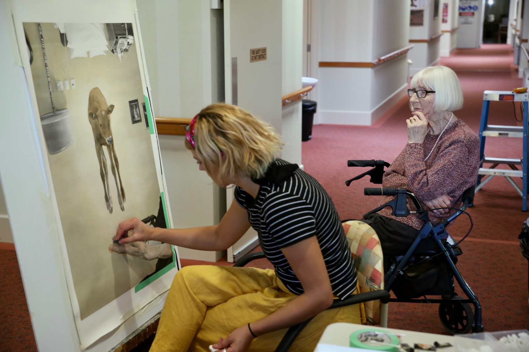 Artist Georgie Mattingley works while Bupa Aged Care resident watches on