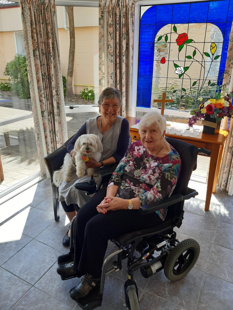 Volunteer Marie Gunn with resident Judith Monty and Honey the dog
