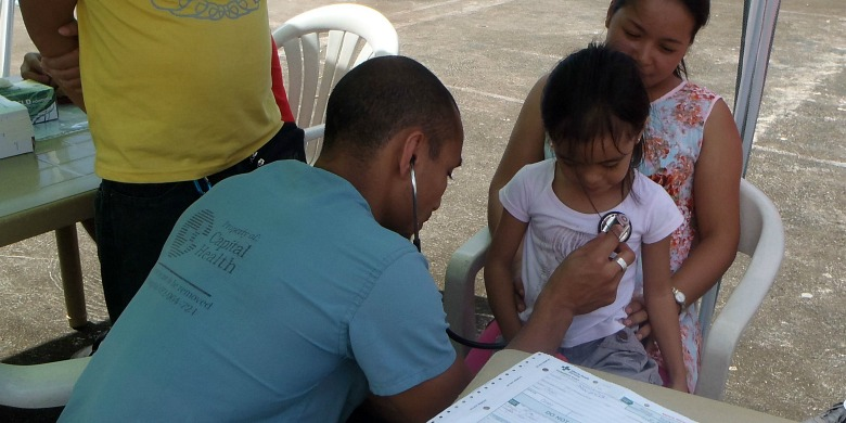 Rashad Chin treats a young patient during his three-week emergency relief mission to the Philippines.