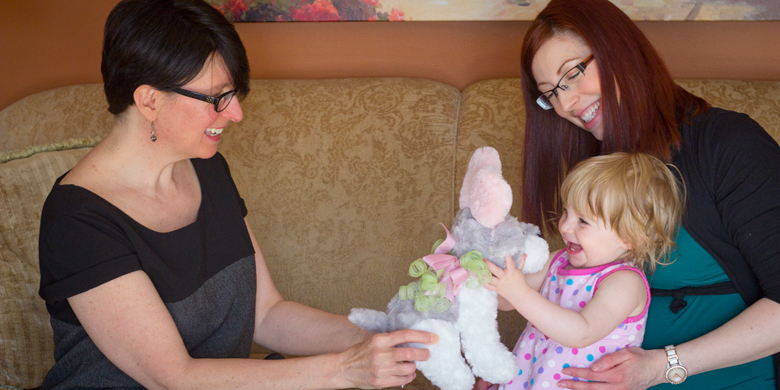 Dawn Kingston (left) and Lana Berry play with Berry's one-year-old daughter Kristen at the Berry family's home.