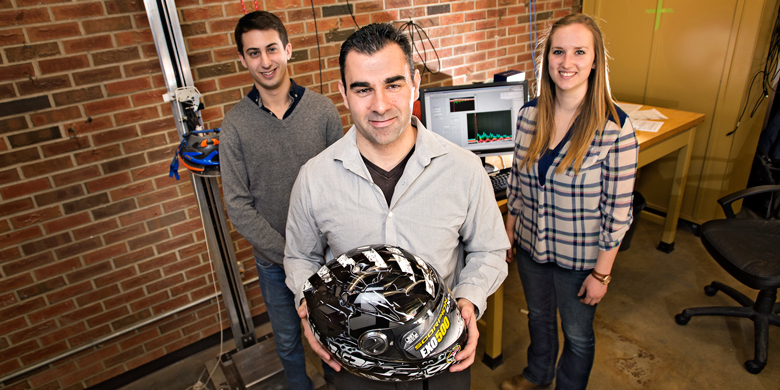 High-impact research: Christopher Dennison (middle) with graduate students Robert Butz and Brooklyn Knowles. Dennison received $60,000 from CFI for a project aimed at making helmets better at protecting against head and brain injuries. (Photo: Richard Siemens)