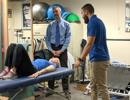Researcher Doug Gross (centre) looks on as his rehabilitation science master's student, Alexander Bell-Moratto, leads patient Jodi Lopetinsky through exercises for lower back pain. (Photo: Sean Townsend)