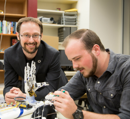 "Patrick Pilarski and MSc student Dylan Brenneis work on a bionic hand in the BLINC Lab. Their goal is for users to ""truly own their prosthetic limbs, to feel like that limb is part of themselves,"" says Pilarski. (Photo: Michael Leenheer, New Light Photography)"