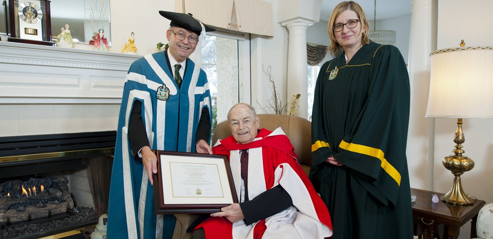 Former premier Don Getty receives a University of Alberta honorary degree in a private home ceremony in 2013 from chancellor Ralph Young and university registrar and vice-provost Lisa Collins.