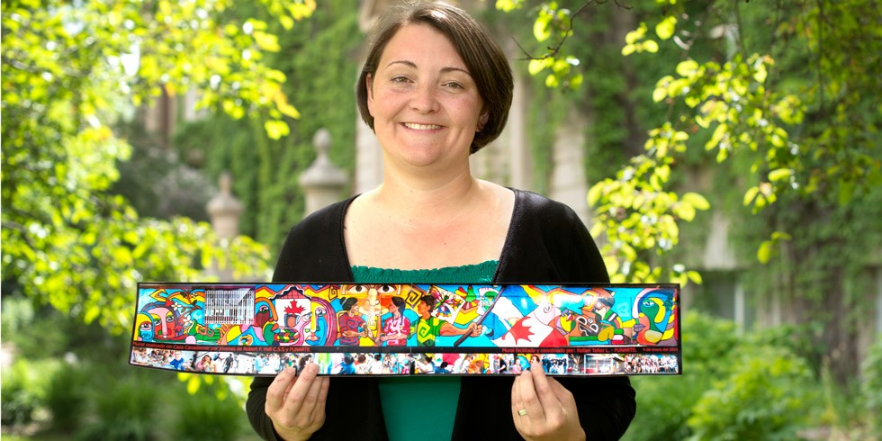 Erin Kelly holds a reproduction of the wall mural at Casa Canadiense in Managua, Nicaragua, where she worked for two years as a global education co-ordinator. (Photo: Richard Siemens)