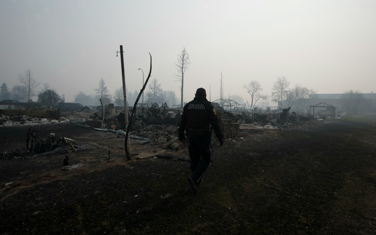 A Wood Buffalo peace officer walks through thick smoke in  in the Beacon Hills neighbourhood in Fort McMurray on Saturday, May 14, 2016. AHS has issued an air-quality advisory for the Fort McMurray area.Travel into the city is still restricted to emergency response and essential services only. (photograph by Chris Schwarz/Government of Alberta)
