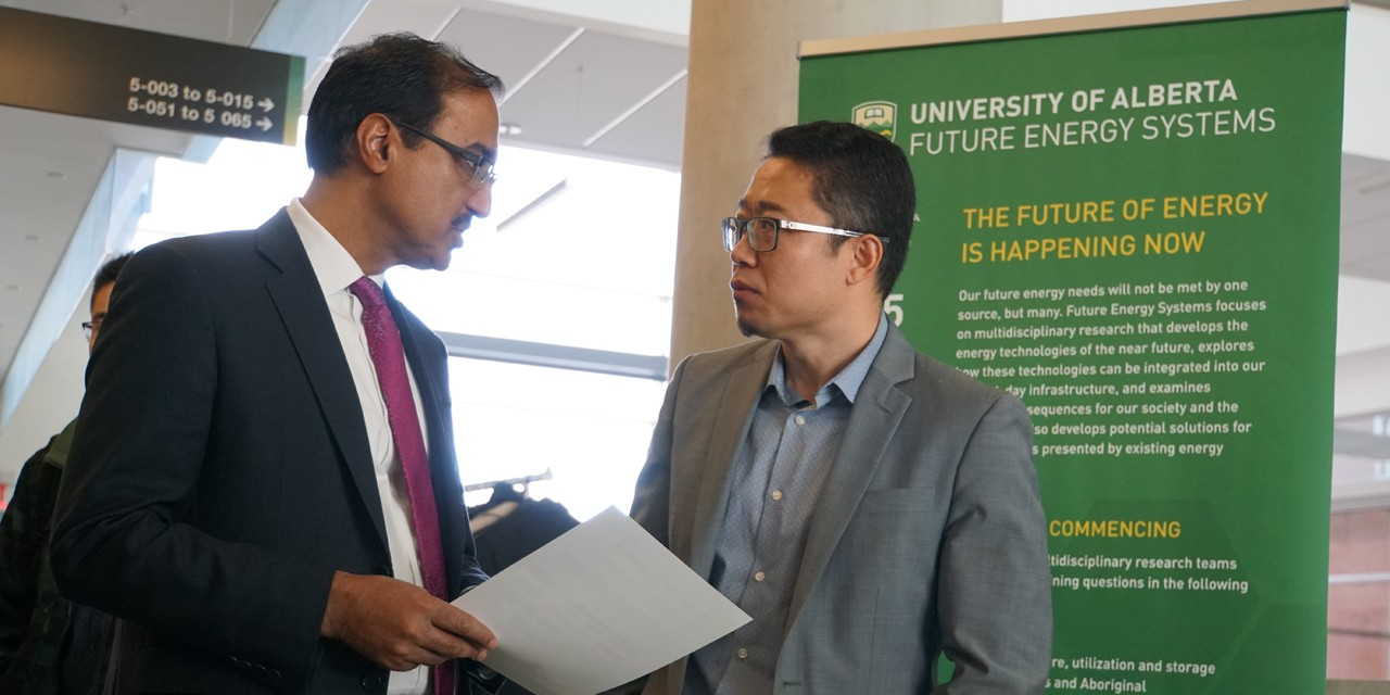 Amarjeet Sohi, minister of infrastructure and communities, talks power grids with electrical engineering researcher Ryan Li at today's CFI funding announcement. (Photo by Kenneth Tam, Future Energy Systems)