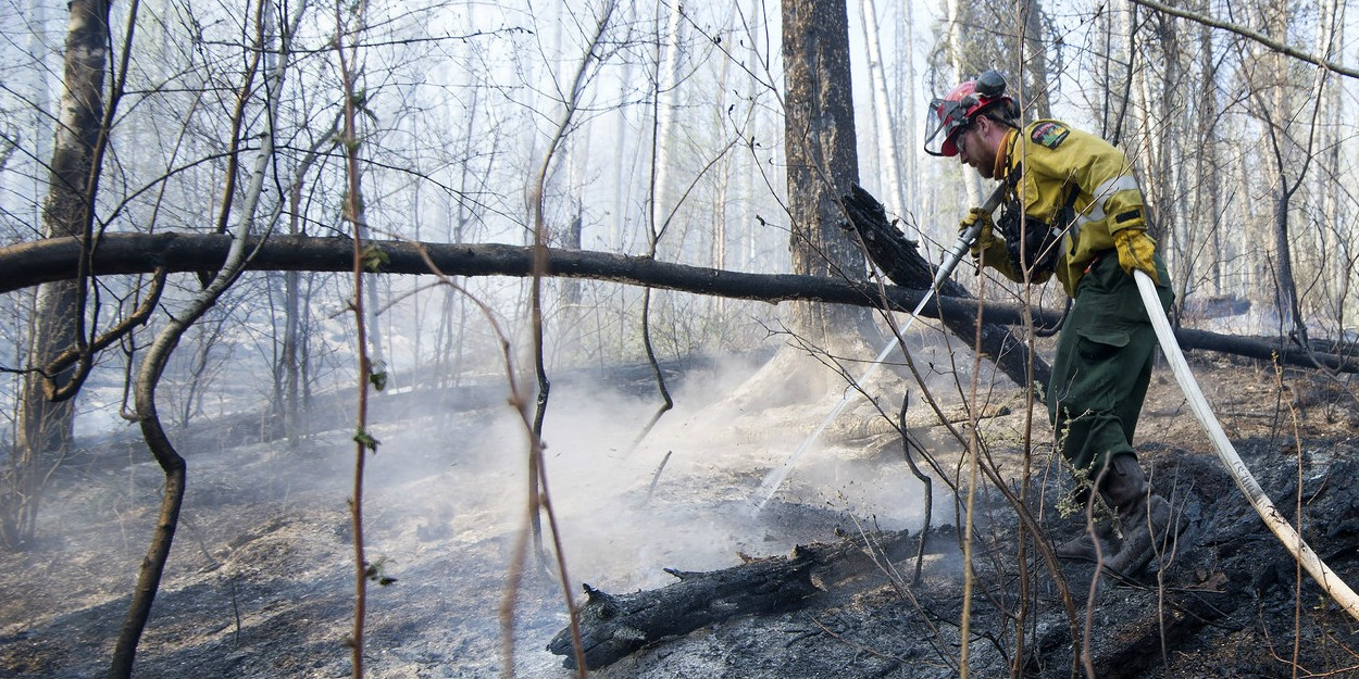 A firefighter with Wildfire Management Alberta's Wild Mountain Unit hoses down hotspots near Fort McMurray in May 2016.
