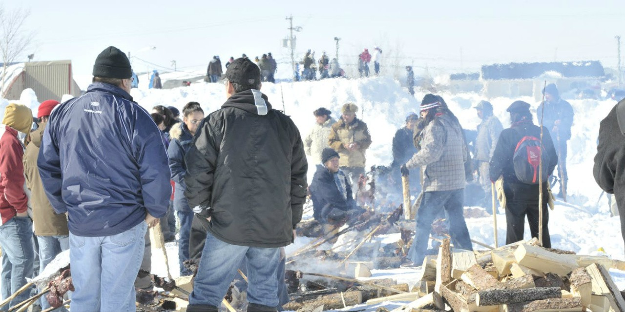 "Members of the James Bay Cree gather around the fire as part of a week-long celebration called ""wellness week,"" aimed at improving personal health and wellness in their community in northern Quebec. (Photo: David Dyck Fehderau)"