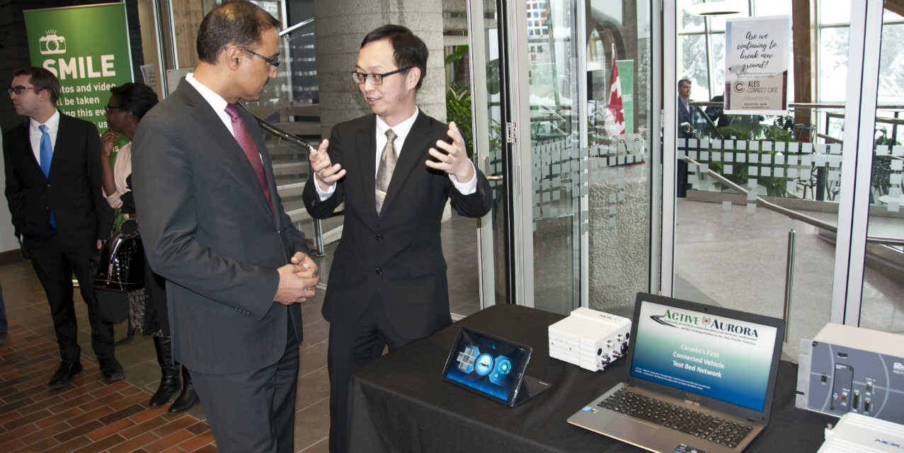 Transportation engineering researcher Tony Qiu describes his ACTIVE-AURORA connected vehicle technology to Minister Amarjeet Sohi at a funding announcement today. (Photo: Michael Brown)