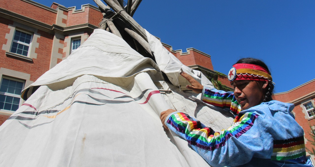 Joe Cardinal of the Alexis Nakota Sioux Nation helps stitch the painted canvas around the tipi that was raised today in front of Pembina Hall, home of the U of A's Faculty of Native Studies. (Photo: Jordan Cook)