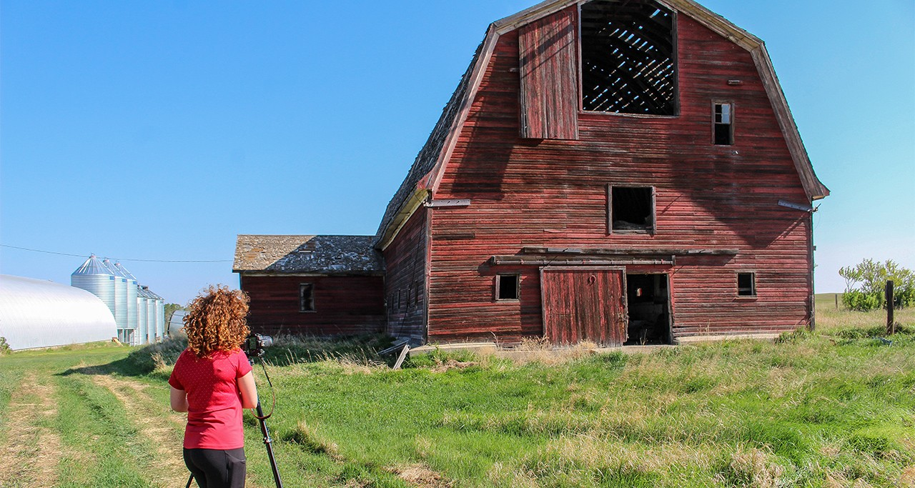 Sydney Hampshire photographs one of the hundreds of historical barns dotting Flagstaff County in east central Alberta for her book project. (Photo: Cary Castagna)