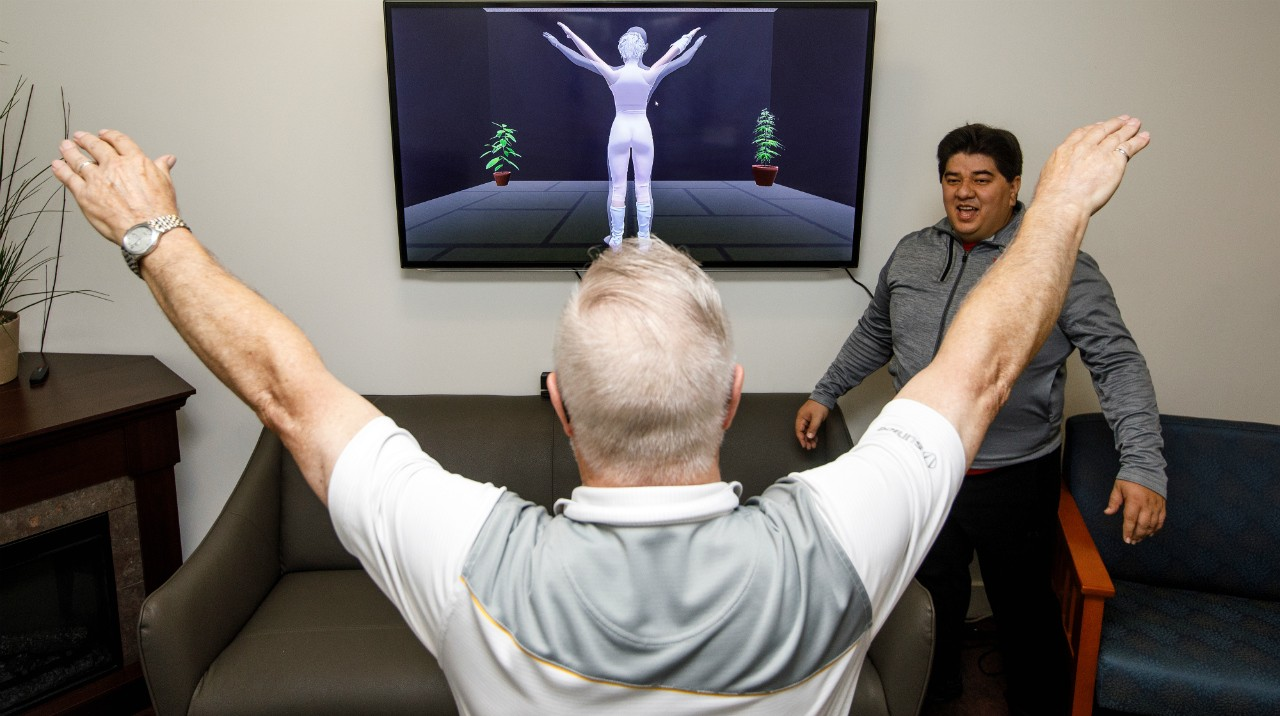 Stuart Embleton performs arm raises with guidance from the VirtualGym program as computing science researcher Victor Fernandez-Cervantes looks on. Feedback from Embleton and other seniors is helping U of A researchers refine the program to deliver customized physical therapy for seniors at home. (Photo: AGE-WELL)
