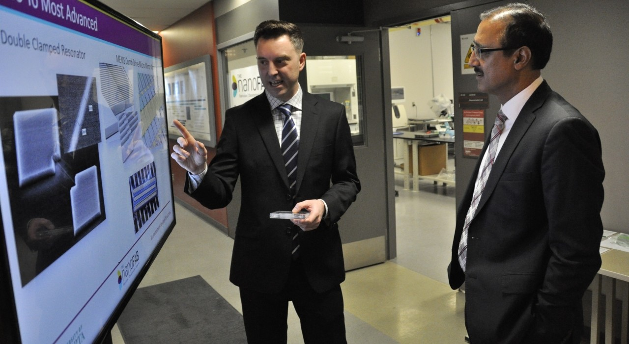 NanoFAB director Eric Flaim (left) shows Natural Resources Minister Amarjeet Sohi some of the devices nanotechnology companies can manufacture at the U of A facility, which received a total of $3.4 million in new funding today to expand its capacity to commercial scale. (Photo: Michael Brown)