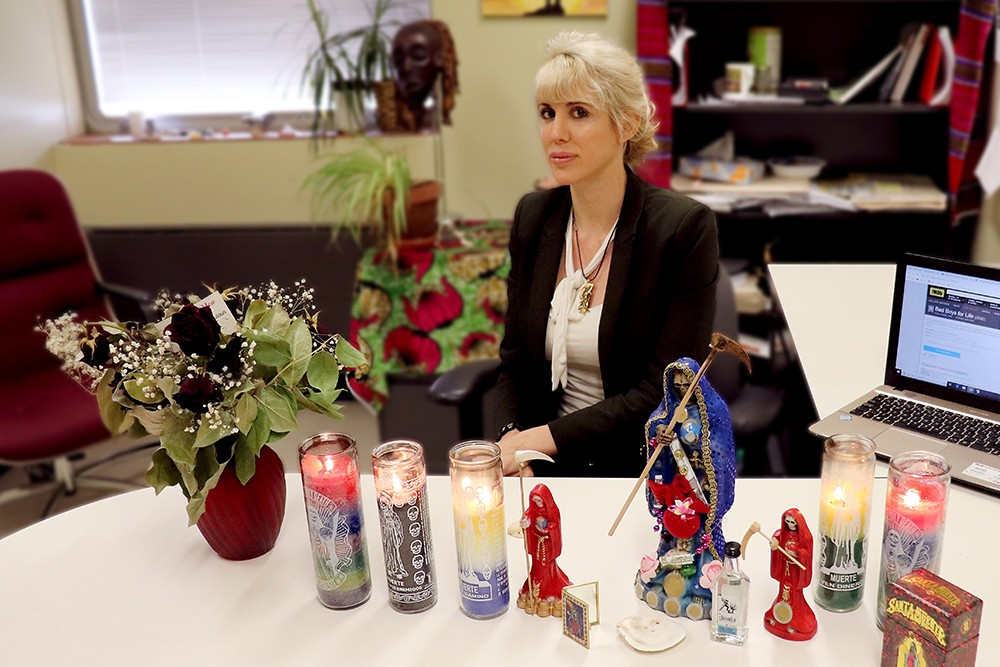 Anthropologist Kate Kingsbury displays some of her collection of Santa Muerte icons, along with offerings including votive candles, flowers and tequila. (Photo: Michael Brown)
