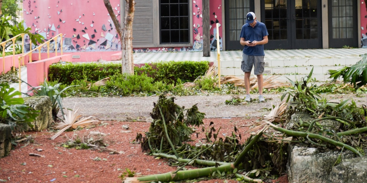 A man uses a smartphone after Hurricane Irma passed through South Florida in September 2017. U of A researchers found location-based social networks like Twitter provide data that could help relief organizations respond more quickly and allocate resources more efficiently during and after disasters. (Getty Images)