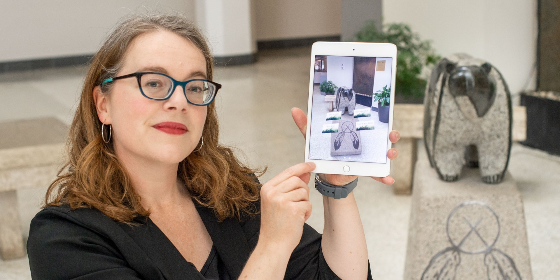 Master's student Amanda Almond shows how a new augmented-reality app lets users access video stories by hovering their electronic devices over the Sweetgrass Bear sculpture at the U of A's Enterprise Square campus in downtown Edmonton. (Photo: Richard Siemens)