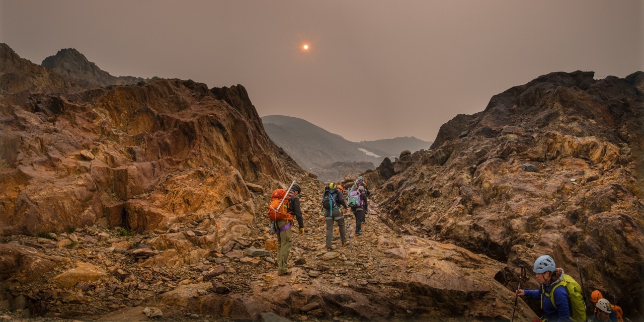 Haze from wildfire smoke obscures the sun as U of A researcher Zac Robinson leads students on a hike in B.C.'s Monashee Mountains in August 2018. Robinson is one of the editors of a new report focusing on how wildfires are affecting Canada's alpine regions. (Photo: Mary Sanseverino)