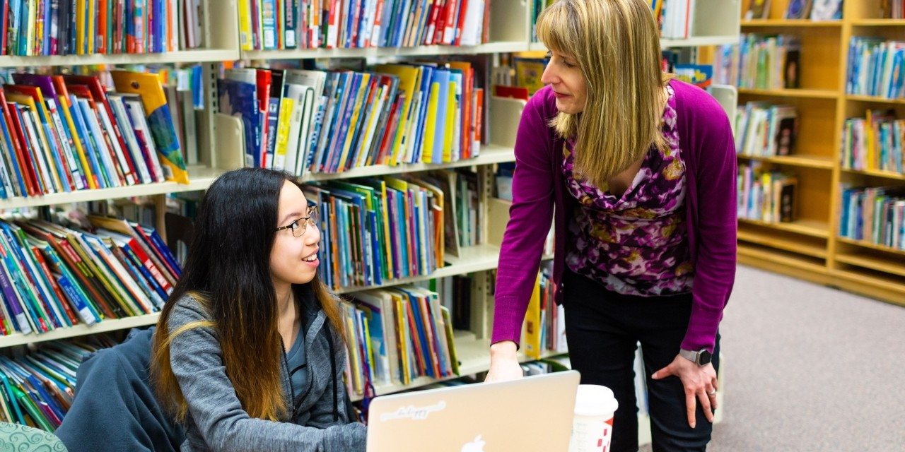 U of A public service librarian Kim Frail (right) speaks with a student in the H.T. Coutts Library, where nearly 16,000 Canadian children's books are now available to be lent out to the public. (Photo: Lauren Dary, L Photography)