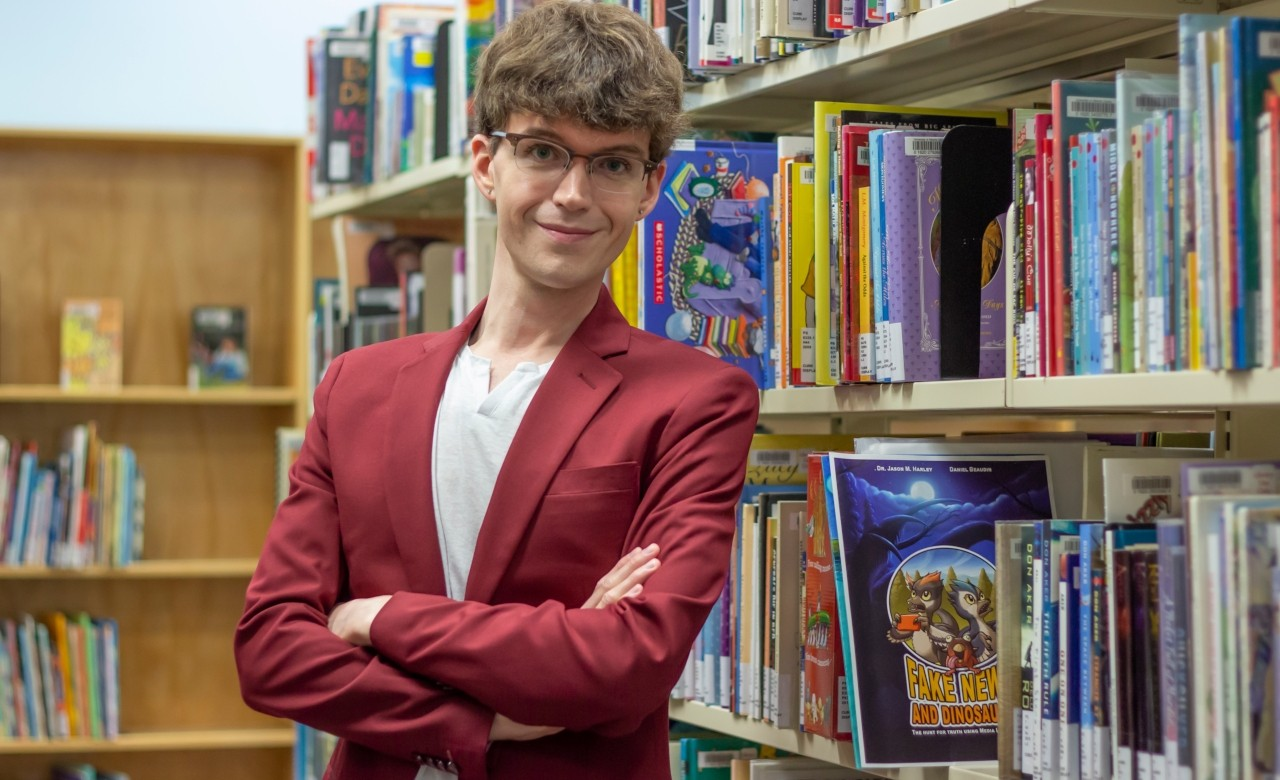 "Educational psychologist Jason Harley with ""Fake News and Dinosaurs."" Harley and illustrator Daniel Beaudin created the graphic novel to  help young readers think critically and separate fact from fiction. (Photo: Laura Sou)"
