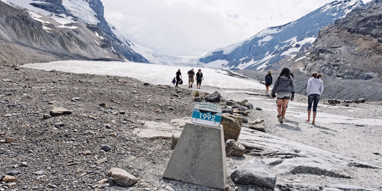 Tourists hike up a trail leading to the toe of the Athabasca Glacier in the Canadian Rocky Mountains, which is receding quickly due to climate change. A marker shows the position of the glacier in 1992. (Photo: Getty Images)