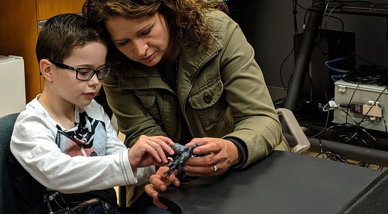 Eight-year-old Mason Thomas and mom Brandie Thomas get their first look at a 3-D printed model of Mason's damaged heart, which was replaced two years ago. A team at the U of A created the models as a way to help Mason understand why his old heart didn't work and why he needed a new one. (Photo: Sean Townsend)