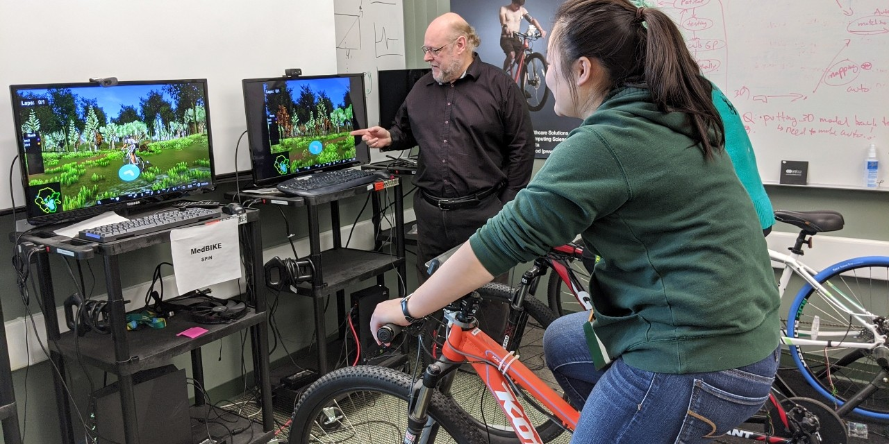 Pierre Boulanger (left) and research assistant Comet Li demonstrate a virtual spin class using MEDBike. The system can remotely monitor blood pressure, oxygen levels and heart activity in recovering cardiac patients as they ride the stationary bike. (Photo: Sean Townsend)
