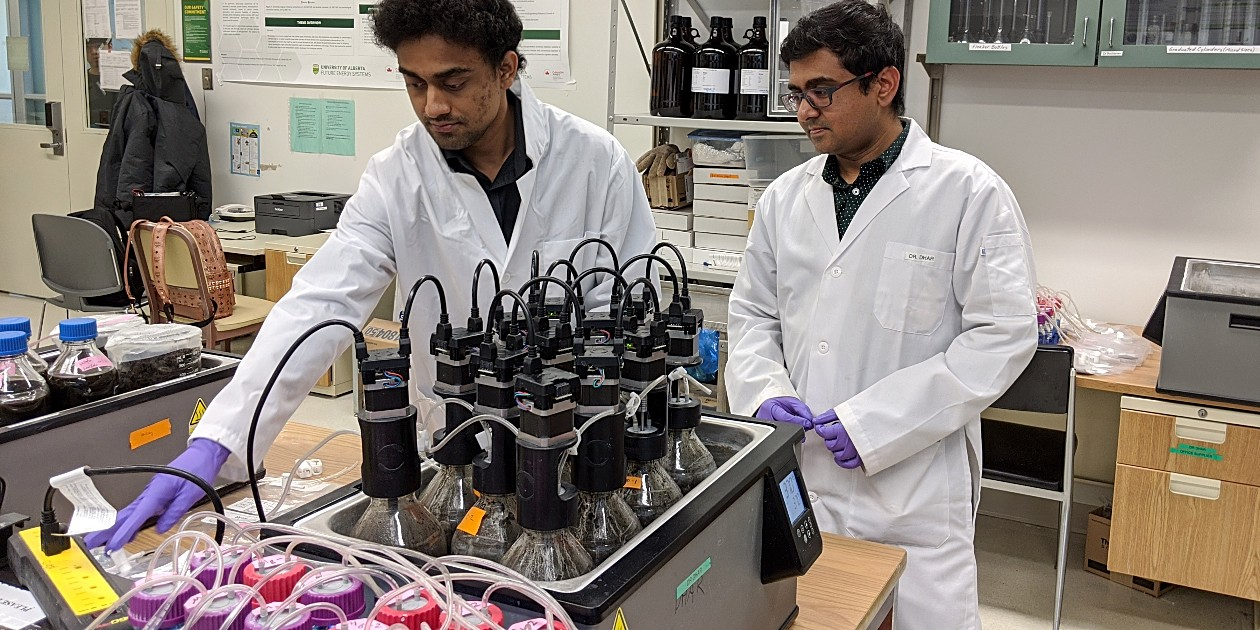 "Environmental engineering master's student Bappi Chowdhury (left) and supervisor Bipro Dhar in the lab with a ""digester"" they are developing that uses microbes to convert a mixture of food waste and fat, oil and grease into renewable biomethane. (Photo: Sean Townsend)"