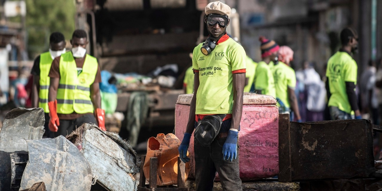 Municipal workers block the streets of the Medina neighbourhood of Dakar, Senegal, on March 22, 2020, as a bulldozer demolishes informal shops in an effort to stop the spread of the coronavirus. (Photo: AP/Sylvain Cherkaoui)